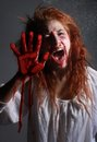 Horror themed image with bleeding freightened woman in situation bloody face Royalty Free Stock Photos