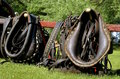 Horse collars and harnesses leather reins lean against a red hitching post of a wagon Stock Photography
