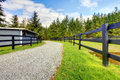 Horse farm with road, fence and shed. Royalty Free Stock Image