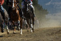 Horse race a on a dirt road a nice background with some mountains and pines Stock Photos