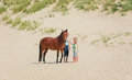 Horse with rider and two girls on the North Sea Texel beach