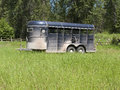 Horse trailer in tall green grass Royalty Free Stock Photo