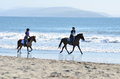 Horseback on the beach two young girls enjoying a ride along Stock Photo