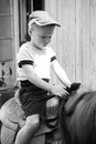Horseback riding little boy ride a pony the fun and the joy of walking through the woods Stock Images