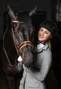 Horsewoman in uniform with a brown horse in the stable. Royalty Free Stock Photo