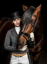 Horsewoman in uniform with a brown horse in the stable Royalty Free Stock Photo