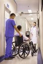 Hospital staff pushing patient in wheelchair Royalty Free Stock Photography