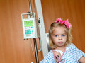 Hospitalized girl recovering little baby with a intravenous bag on a pole real situation Royalty Free Stock Image