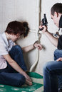 A hostage girl enchained to the pipe woman encased in handcuffs under supervision of abductor Stock Photography