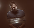 Hostage photo of a young man being held duck taped to the chair shallow dof Stock Images