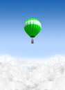 Hot air balloon above the clouds a lonesome green floating on a clear blue sky background Royalty Free Stock Photos