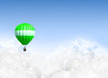 Hot air balloon above the clouds a lonesome green floating on a clear blue sky background Royalty Free Stock Photo