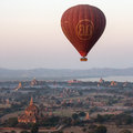 Hot air balloon bagan myanmar flying over the temples of the archaeological zone in in the early morning sunlight in the distance Stock Photos