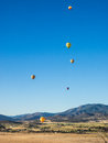 Hot air balloon festival colorful s fly through a mountain valley at the montague fair in northern california Royalty Free Stock Images