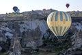A hot air balloon flies down Love Valley at sunrise near Goreme in the Cappadocia region of Turkey.