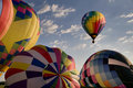 Hot air balloon floating over other inflating balloons one ascending above at a festival readington festival Stock Images