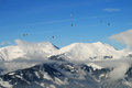 Hot air ballooning over the tops of mountains snowy Royalty Free Stock Photography