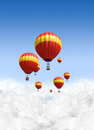 Hot air balloons above the clouds a collection of red and yellow balloon floating on a clear blue sky background Royalty Free Stock Image