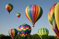 Hot air balloons ascending or launching at a ballooning festival various with colorful envelopes Royalty Free Stock Images