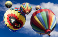 Hot air balloons drifting upward several from the temecula balloon and wine festival into blue cloud filled sky a concept for Royalty Free Stock Image
