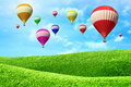 Hot air balloons floating over green field Royalty Free Stock Photo