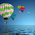 Hot air balloons flying over the ocean Stock Image