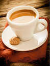 Hot aromatic morning espresso coffee serving of served in a plain white cup with a macaroon on a rustic cloth and old grungy Royalty Free Stock Photos