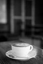Hot art Latte Coffee in a cup on wooden table, black and white t Royalty Free Stock Photo