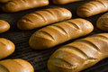 Hot baked breads on a line fresh bread loafs the production Royalty Free Stock Images