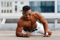 Hot Beautiful black guy with bulging muscles posing against the backdrop of the urban landscape. Man fitness model with a beautifu Royalty Free Stock Photo