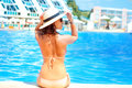 Hot beautiful woman in hat and bikini standing at pool with her arms raised to her head enjoying looking view of swimming ocean on Stock Images