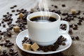 Hot black coffee in a white cup, cane sugar and roasted beans Royalty Free Stock Photo
