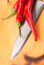 Hot capsicum chili pepper and knife on board Stock Photo