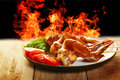 Hot chicken bbq wings with vegetables on the plate and fire on background Stock Image