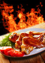 Hot chicken bbq a wings with vegetables on the plate and fire on background Royalty Free Stock Photo