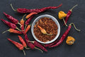 Hot chili peppers a group of dried and seeds habanero jalapeño rawit bird's eye thai on a piece of black slate Stock Images