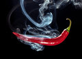 Hot chili red pepper with smoke on black background Stock Image