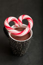 Hot chocolate and candy heart closeup of mug of with hard with red swirls resting on top Stock Photo