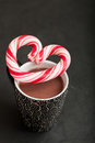 Hot chocolate and candy heart closeup of mug of with hard with red swirls resting on top Royalty Free Stock Photos