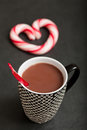 Hot chocolate and candy heart closeup of mug of with red plastic spoon hard with red swirls in background Stock Photos