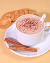 Hot chocolate drink milk cinnamon and biscuit on a yellow background Royalty Free Stock Photo