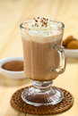 Hot chocolate with whipped cream and shavings on top cocoa powder and cookies in the back selective focus focus on Royalty Free Stock Photography