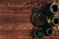 Hot coffee in black cup and turkish pots cezve with beans, saucer with copy space on brown old wooden board background, top view.