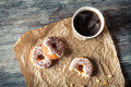 Hot coffee and donuts given in the paper on old wooden table Stock Images