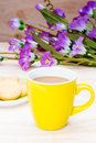 A hot coffee in yello cup and butter cookie on wood yellow board Stock Photo
