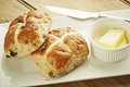 Hot cross bun on white dish and wooden table top Stock Image
