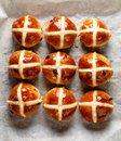 Hot cross buns,freshly baked hot cross buns on white parchment paper, top view. Royalty Free Stock Photo