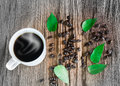 Hot cup of coffee with smoke, coffee beans and green leaves on vintage wooden background Royalty Free Stock Photo