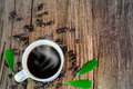 Hot cup of coffee with smoke, coffee beans and leaves on vintage grunge wooden background Royalty Free Stock Photo