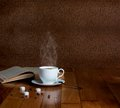 Hot cup of fresh coffee on the wooden table and a stack books to read Royalty Free Stock Image